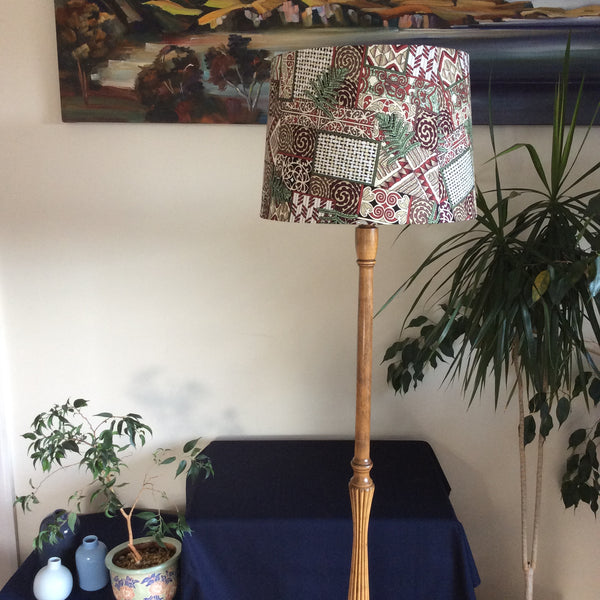 Honey coloured floor lamp with large tapered lampshade in kowhaiwhai fabric