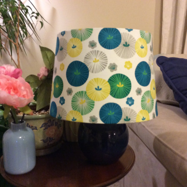 Medium tapered light shade with parasol fabric on small blue lamp stand.