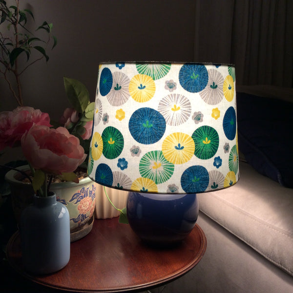 Medium tapered light shade with parasol fabric lit up