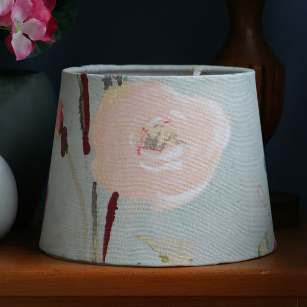 A close up of a cool cream peony on a small tapered lampshade made with the peony fabric.