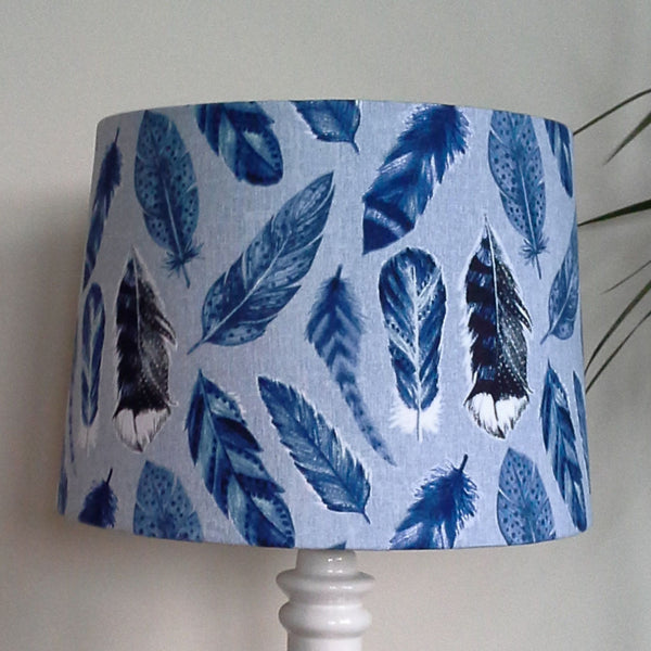 Large blue feather fabric on a large tapered lampshade and white stand.