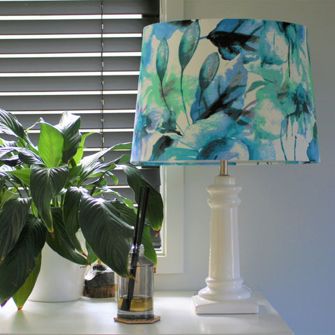 Water colour fabric on a large tapered shade and large white porcelain stand