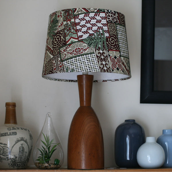 Māori patterns and designs on a medium tapered lampshade and wooden stand.