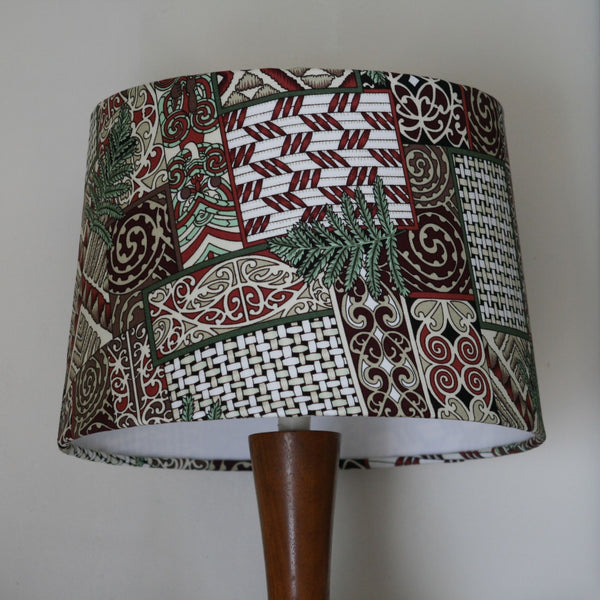 Kōwhaiwhai fabric lampshade on wooden stand close up.