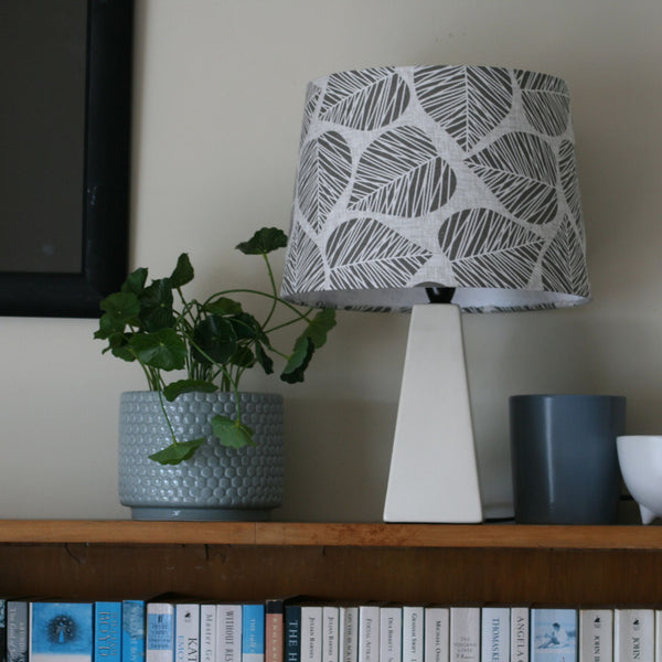 Stencil leaf fabric on medium shade on white lamp stand.