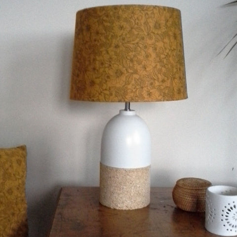 Mustard lampshade with delicate black flowers, medium tapered shade on a medium two tone stand.