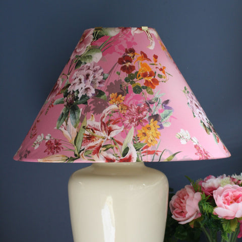 Lilies and asorted flowers in oranges, purple and white on a loud pink background. Fabric on a large conical shade on a large ginger jar stand.