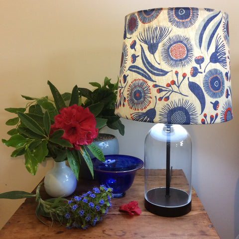 Glass bottle table lamp with proust gum blossom fabric shade