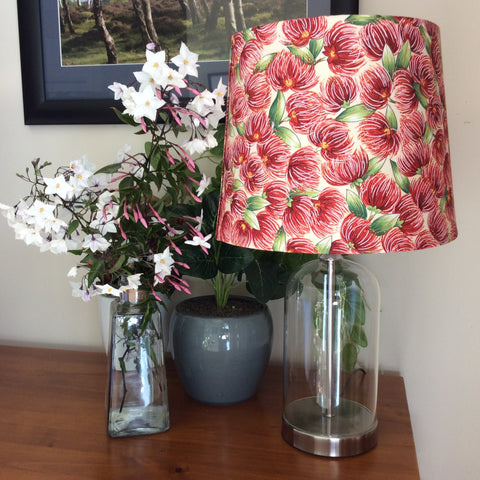 Glass bottle table lamp with pohutukawa blossom cream fabric shade