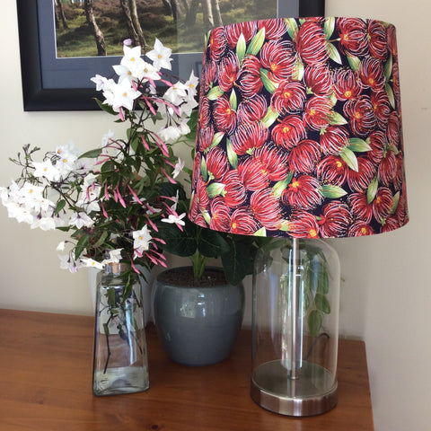 Glass bottle table lamp with pohutukawa navy fabric shade