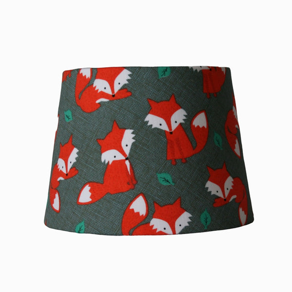 Orange foxes on a small lampshade.