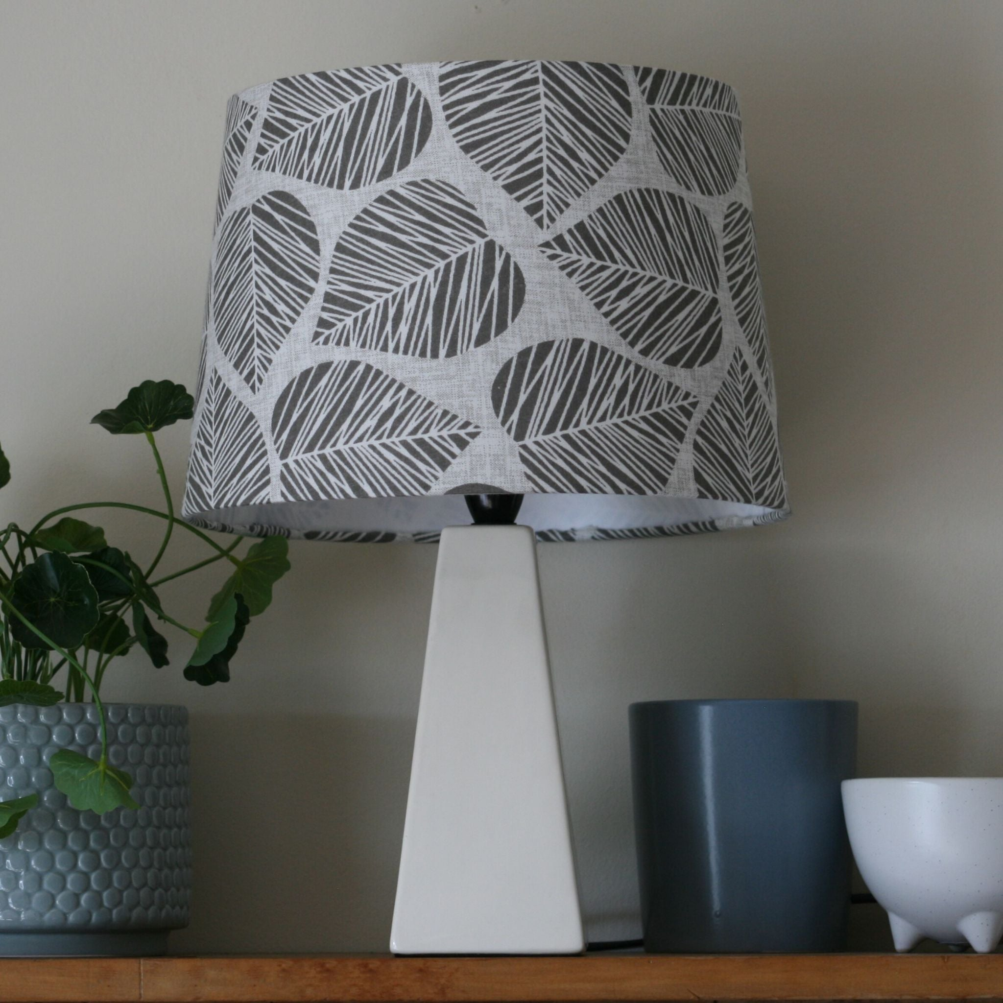 Grey leaves medium lampshade, on white square porcelain base.