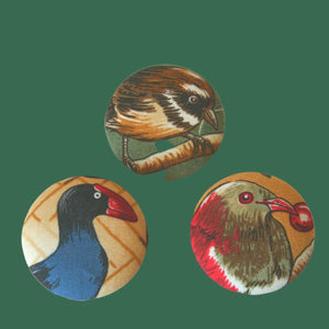 Three badges with three different birds, the fantail or pīwakawaka, the kererū or wood pigeon and the pukeko, or swamp hen.