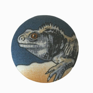 One badge with the face of a tuatara on it, blue background.