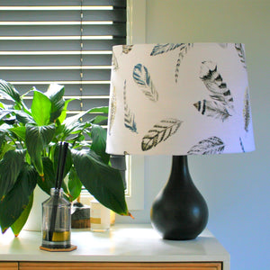 White feather fabric on a large tapered shade on a black ceramic lamp stand.