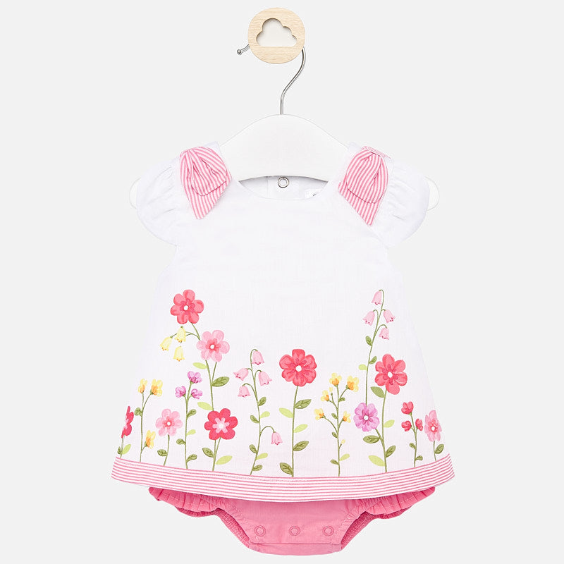 Mayoral Singapore Newborn Girl Dress. A pretty white and pink floral cotton dress for newborn girls by Mayoral. The design features florals on the hem and pretty bows on the shoulders.