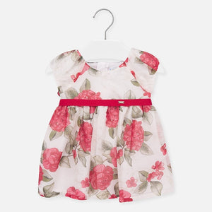 Mayoral Singapore Floral Dress. Little girls ivory dress from Mayoral, with a red and green floral pattern. It is made in sheer polyester voile, with a lightweight cotton lining. There are pretty puffed sleeves and a removable ribbon belt with button fastening.