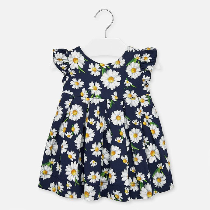 Mayoral Singapore Daisy Dress. Navy blue dress from Mayoral, made in soft cotton. It has a white and yellow daisy pattern and an elasticated waistband. There are pretty ruffles over the shoulders and a bow on the back.
