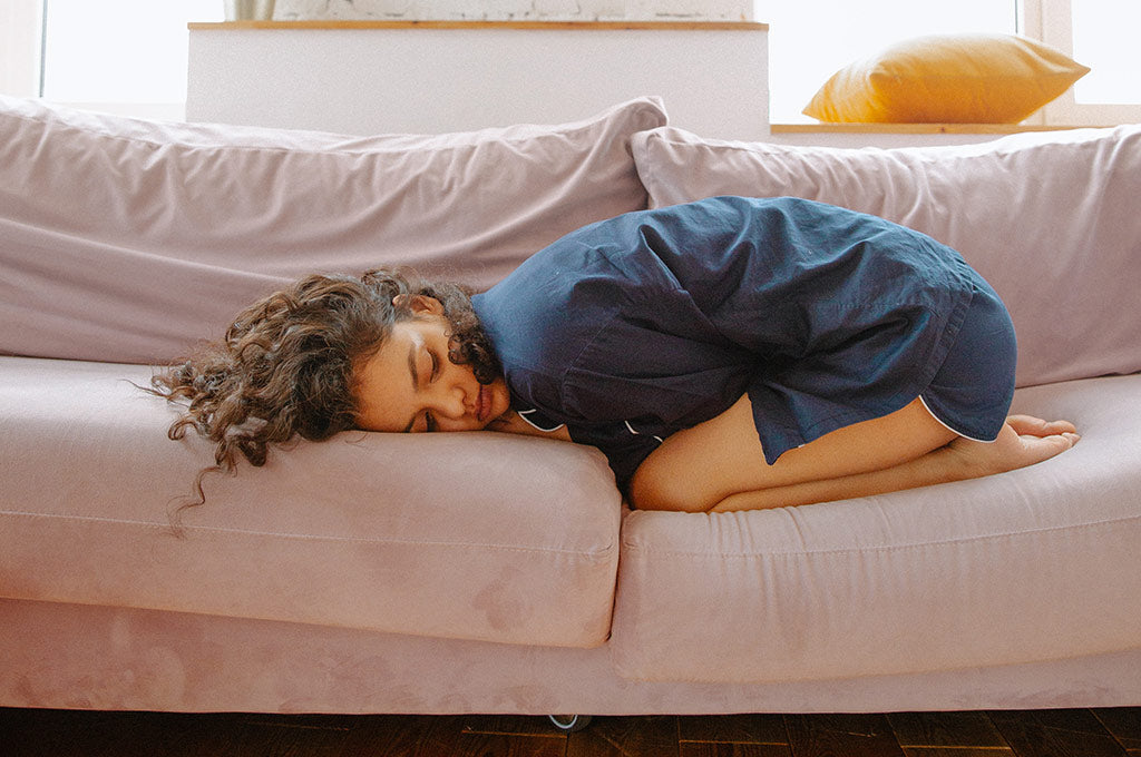 girl in pajamas curled up on couch, indicating period cramps