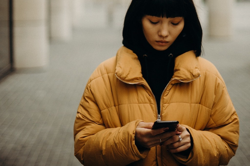 woman wearing a yellow jacket walking on a sidewalk looking down at her phone.