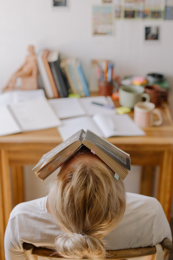 girl sitting in a chair at a wooden desk with a book opened on her face and leaning her head back
