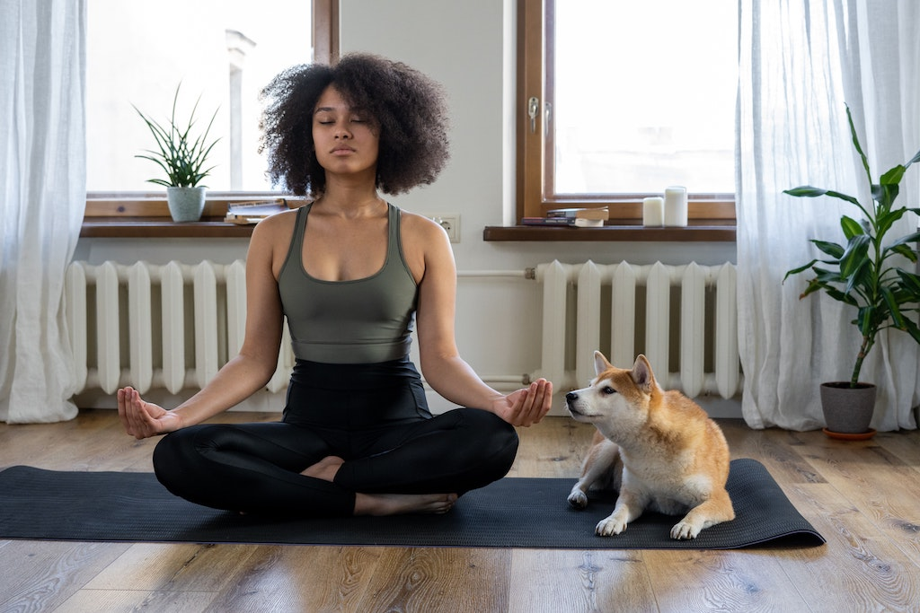 Woman meditating on a yoga mat with dog next to her