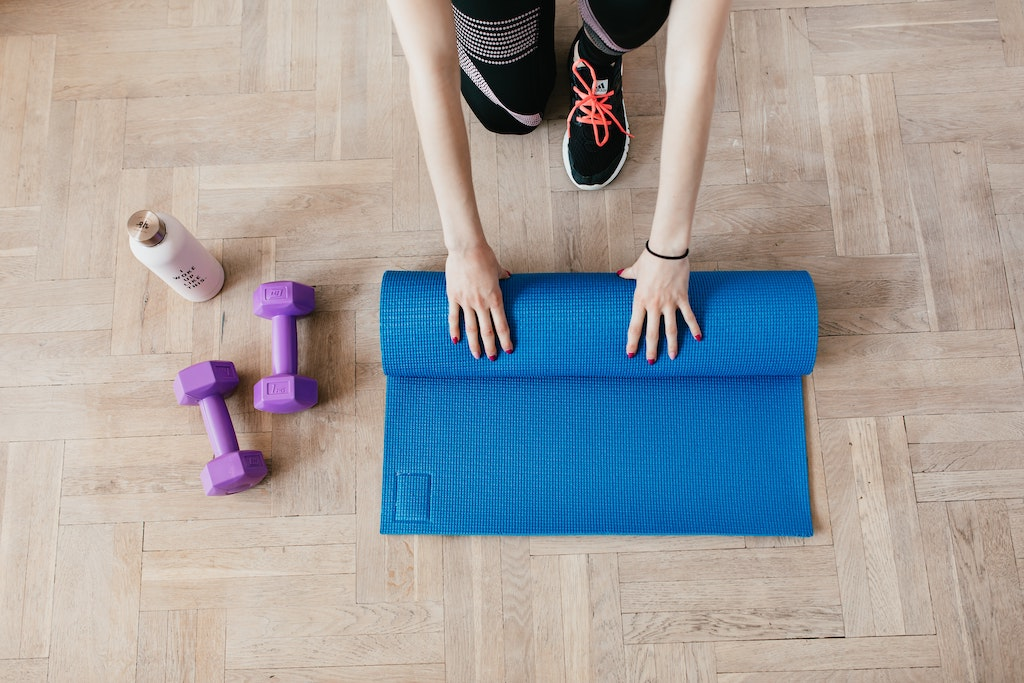 woman rolling up a blue yoga mat on a wooden floor with 2 weights and a water bottle next to her