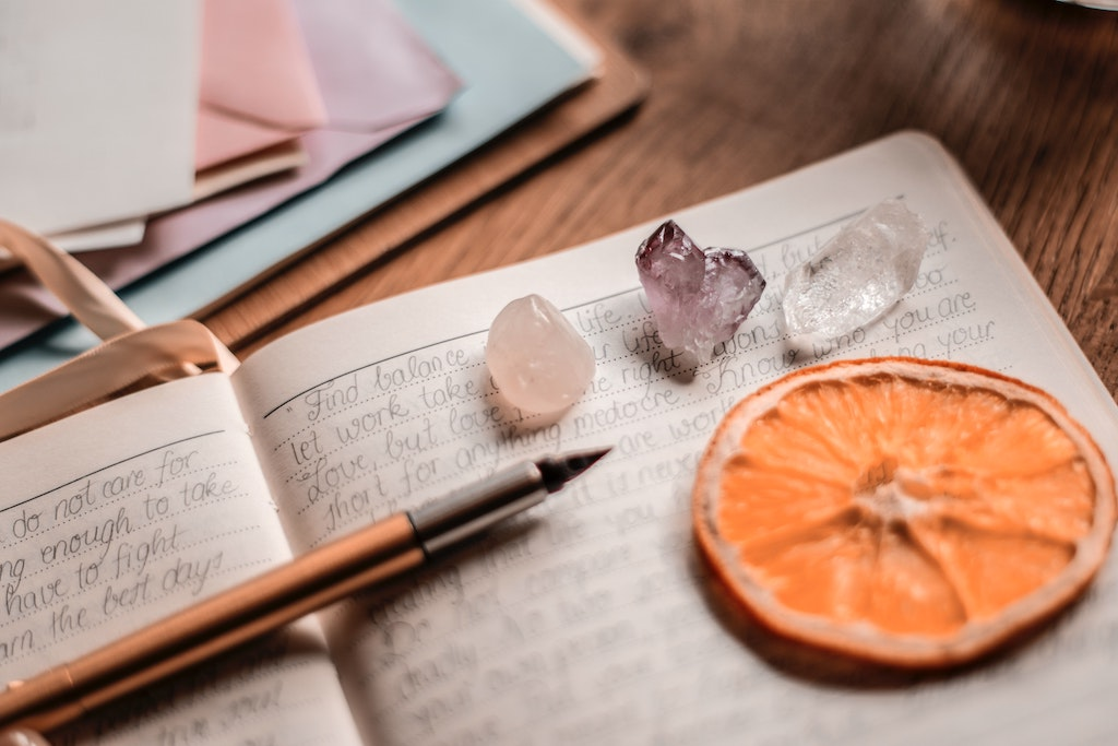 an open journal on a desk with a quill pen and gemstones laying on the open journal