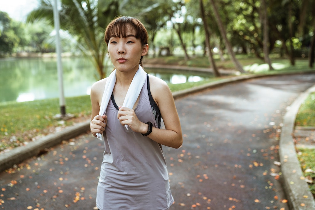 Image of woman wearing a grey tank top and holding a white towel around her neck running in a park setting