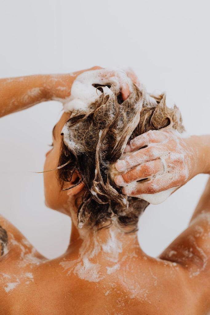 picture from the back of a women with blonde hair in the shower using foaming hair wash and rubbing it into her hair