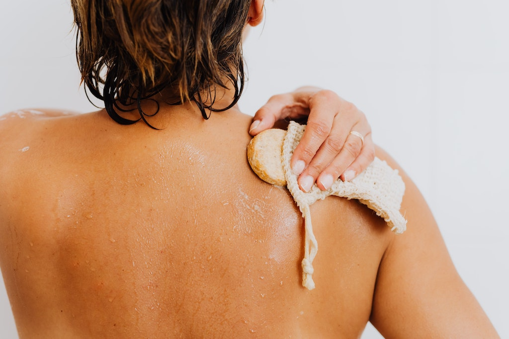 woman in the shower washing her back with a sponge