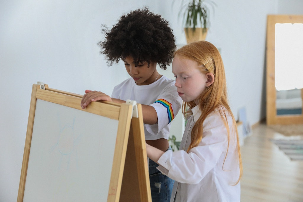 2 young girls both painting together collaboratively