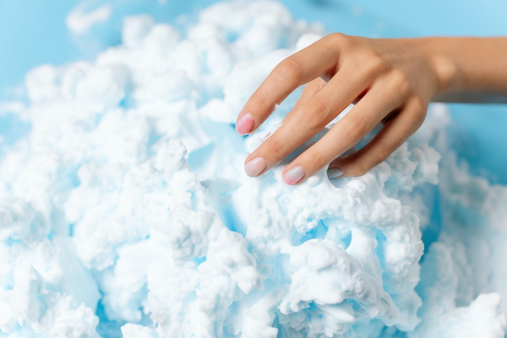 woman with painted fingernails touching a cloudy white fluffy object