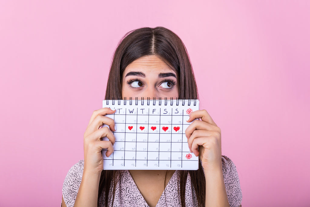 girl holding calendar in front of her face, with red hearts on 5 days of one week to imply her period cycle