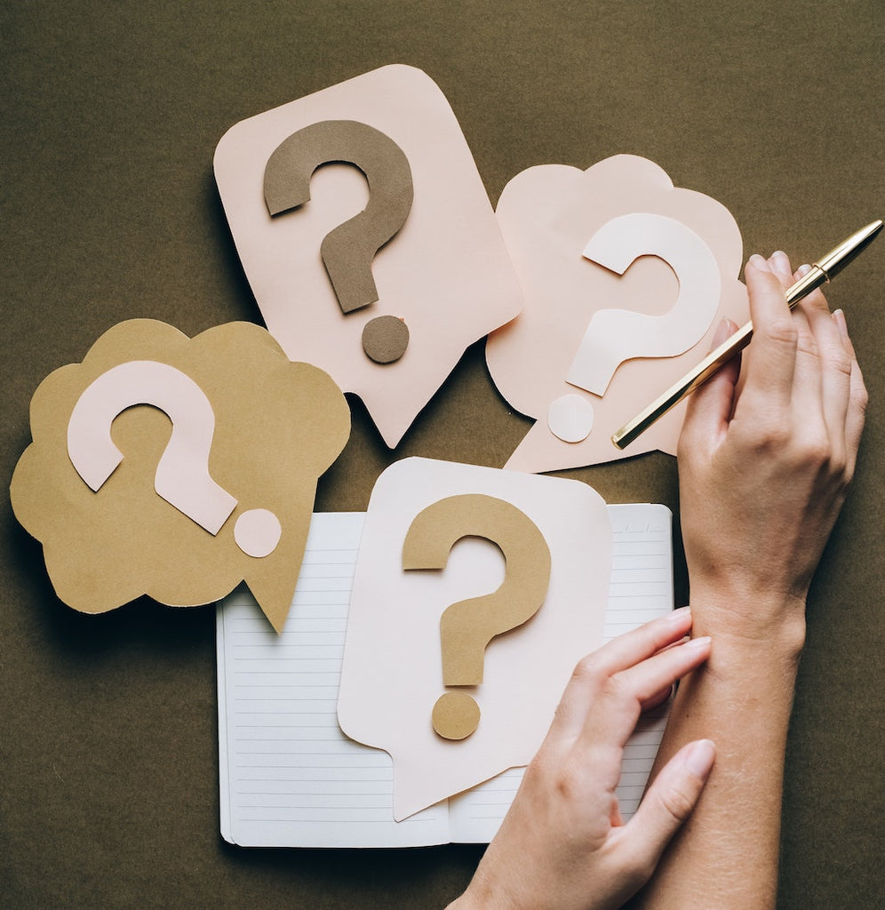 hand hold pen, notebook and paper cutouts of question marks in word bubbles