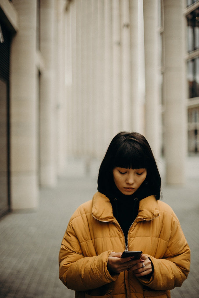 woman walking outside wearing a yellow jacket looking down at her phone