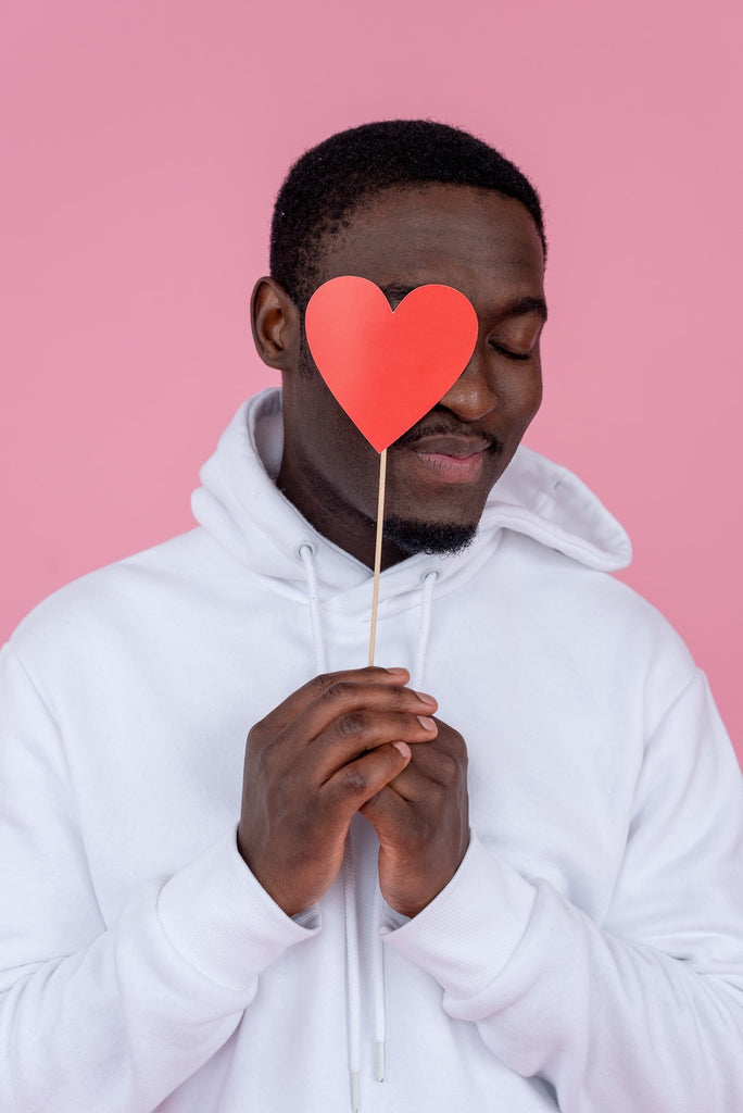 male wearing a white hoodie in a pink background holding a heart on a stick over his face