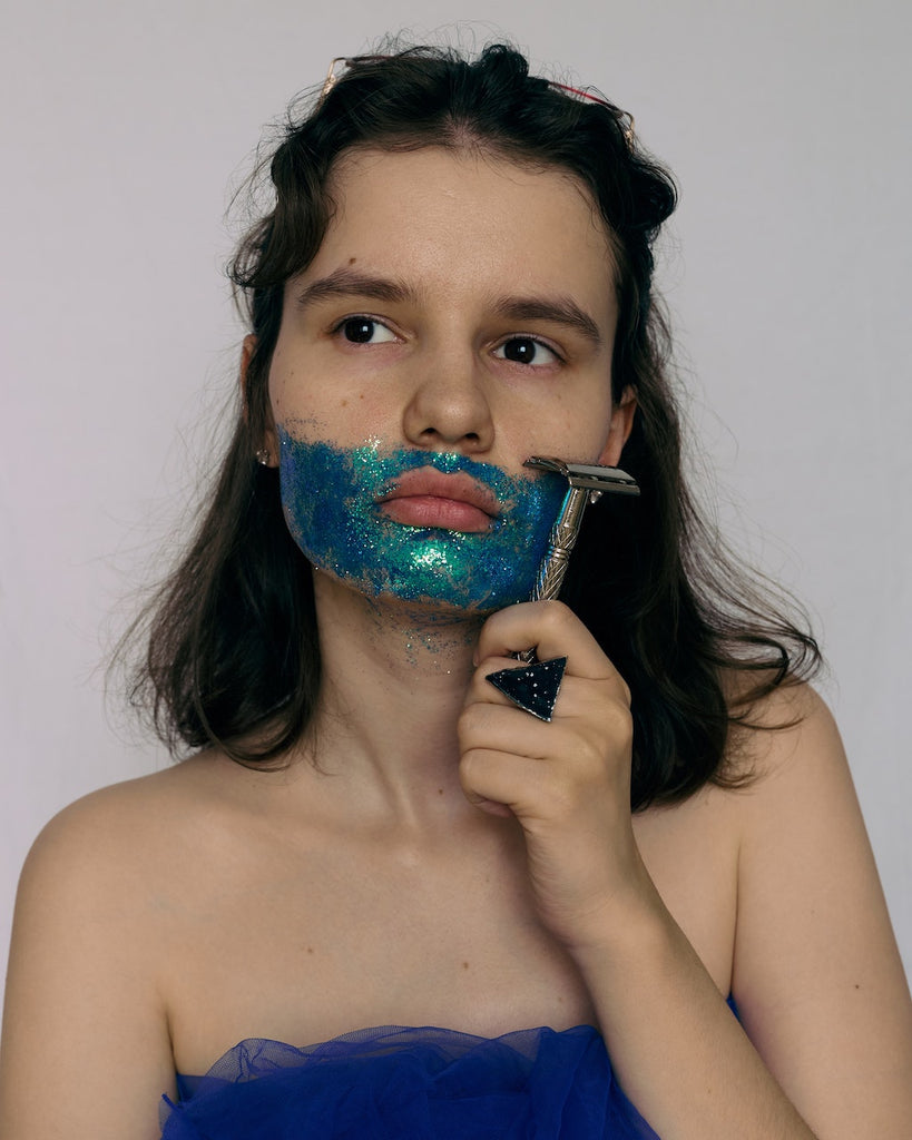 teenage girl with sparkly blue paint on the beard area holding a razor up to her face