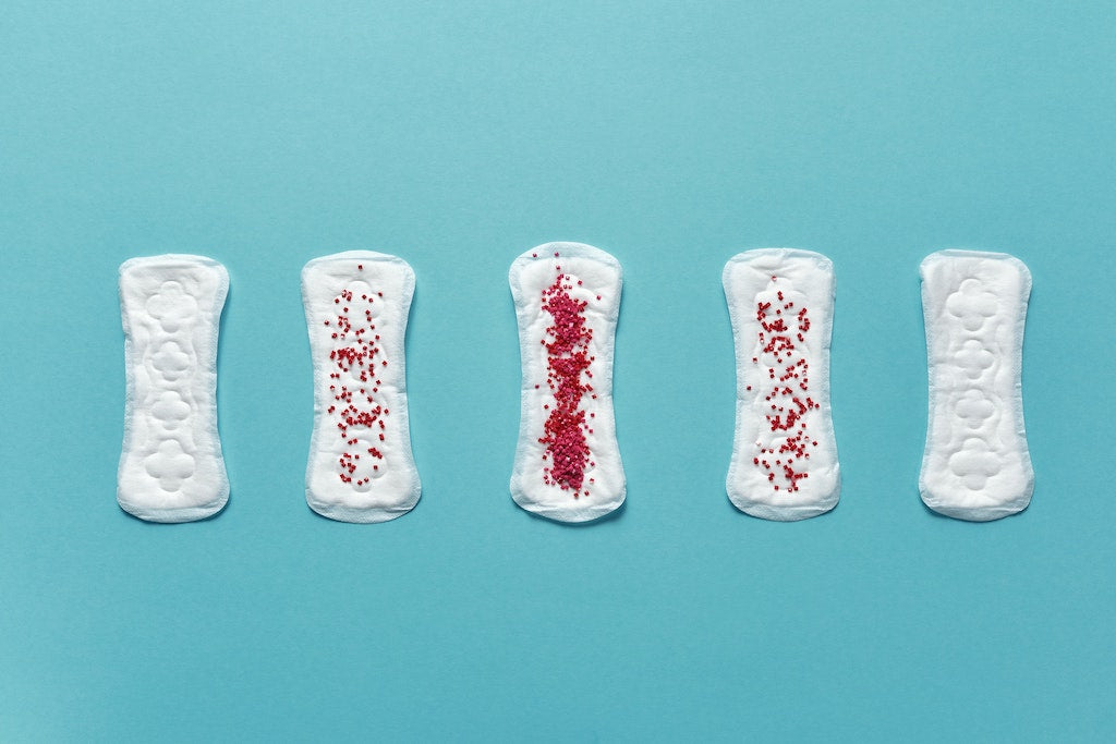 period pads in a row, some with more red beads on it than others
