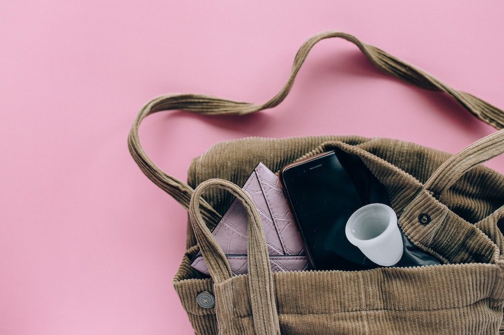 a brown bag with a menstrual cup, cellphone, and wallet sticking out of it with a light pink background