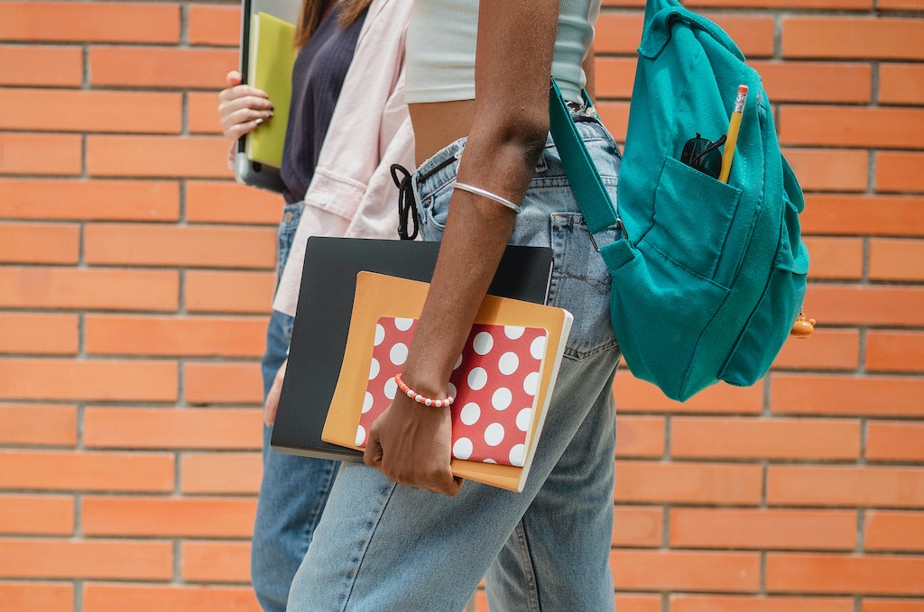 view from the side only showing the torsos of two young girls walking with backpacks and school supplies