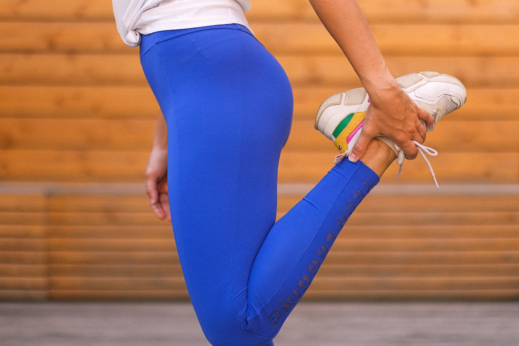 Image of person's legs wearing blue leggings and white sneakers doing a leg stretch that involved holding their foot behind they're back and bending the knee