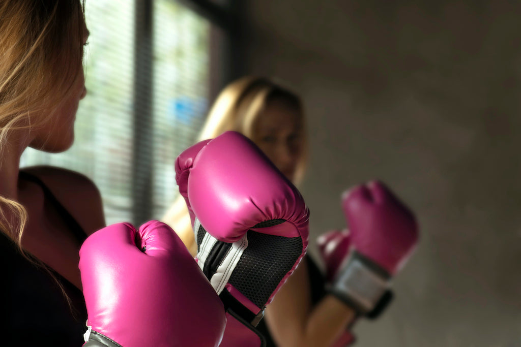 girl looking at herself in mirror wearing pink boxing gloves