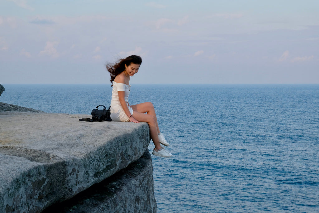 girl in a white dress sitting at the edge of a rock overlooking the water