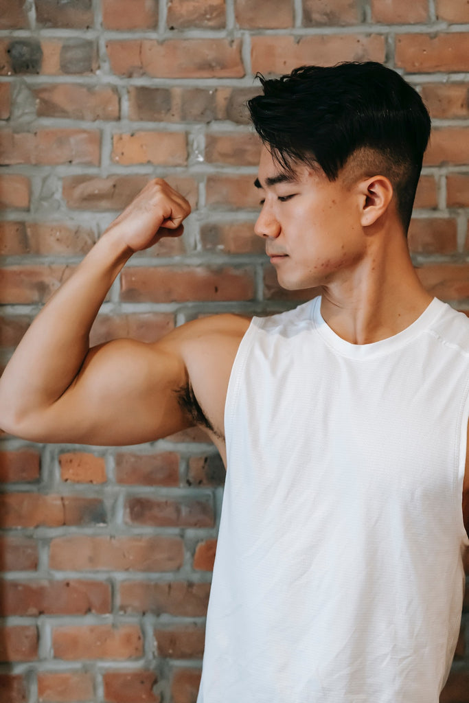 male in a white tank top flexing his bicep