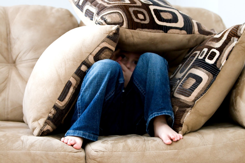 boy sitting on couch hiding under pillows