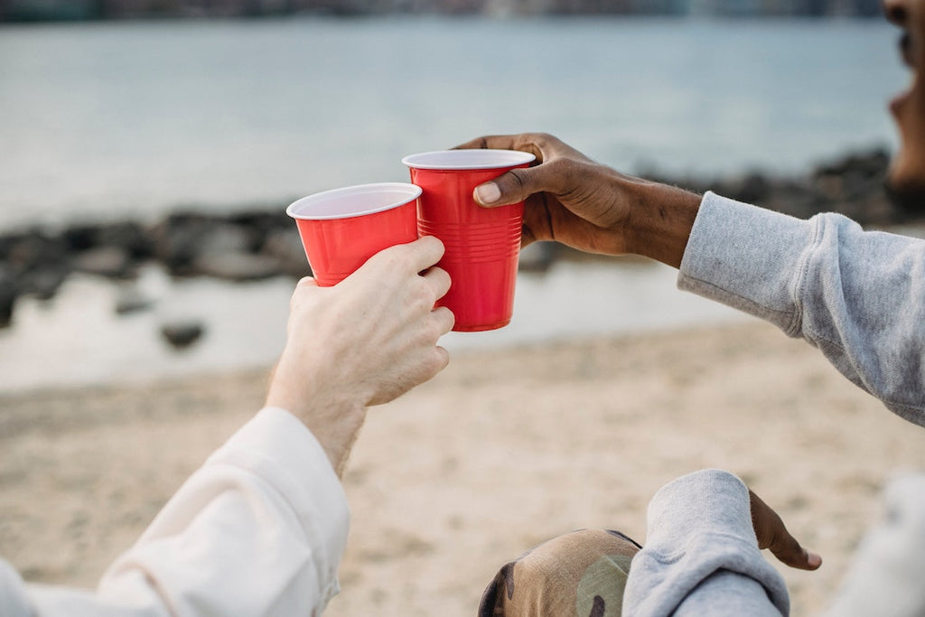 a shot of two people's arms holding solo cups in their hands and clinking them together with a beach background