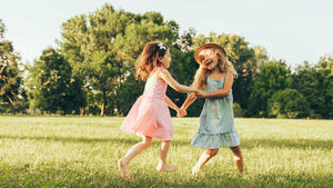 Two young girls wearing dresses while holding hands dancing outside.