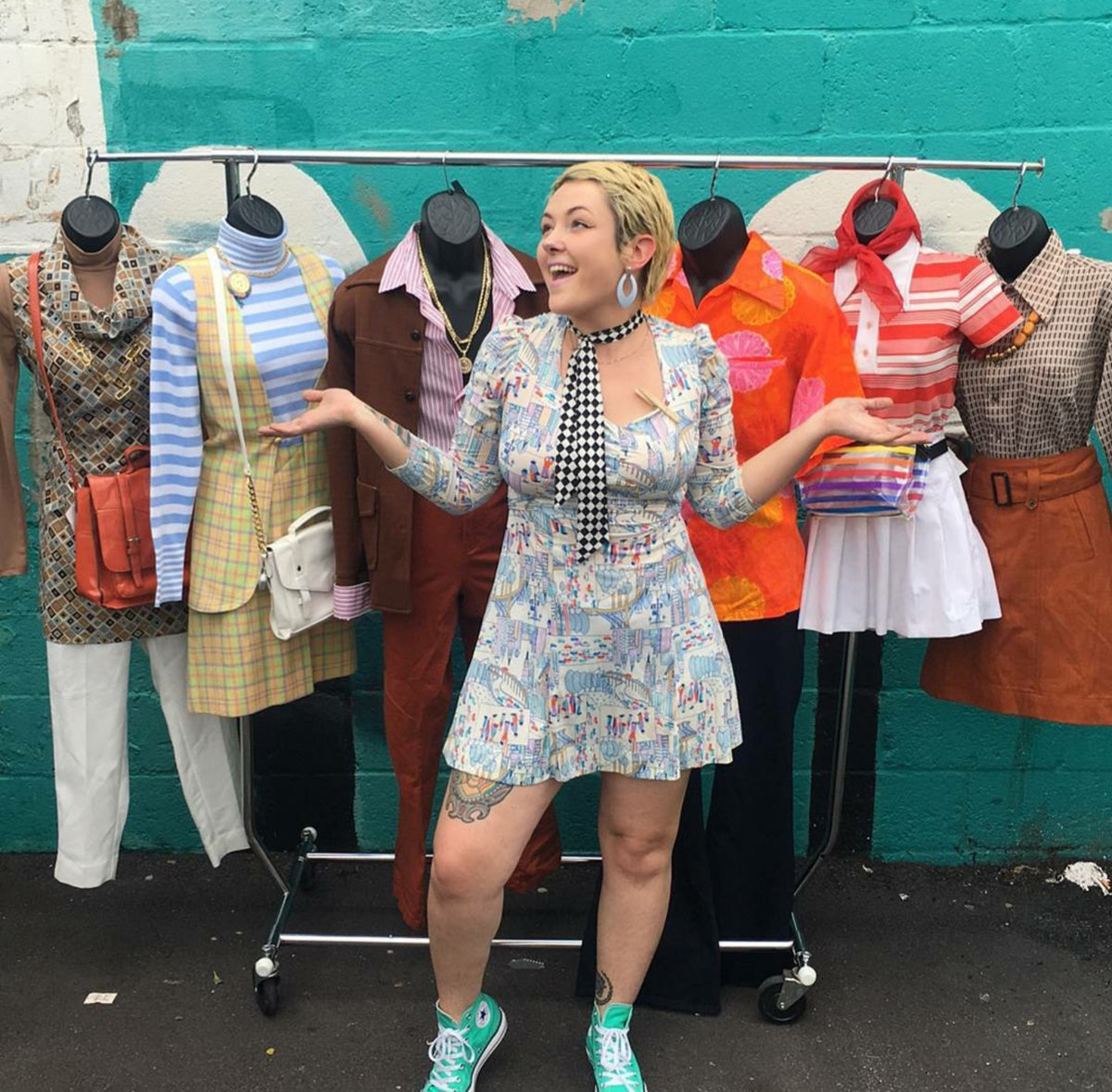 Image of lady in front of rolling rack with half forms dressed in different outfits