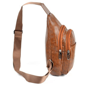 side of brown faux leather sling bag with zipper compartments